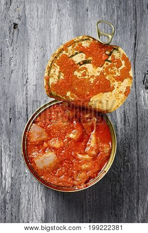 high-angle shot of an open can of spanish oreja de cerdo, a typical stew of pigs ear, on a rustic wooden table