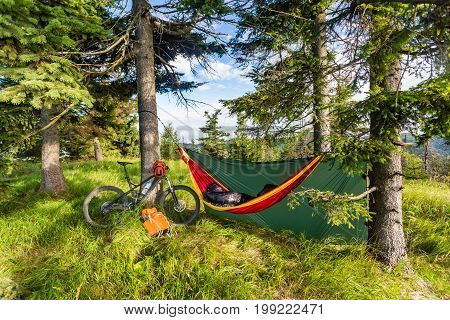 Camping in woods with hammock and sleeping bag on mountain biking adventure trip in green mountains. Travel campsite when mtb cycling with backpack. Lightweight shelter in wilderness forest Poland.