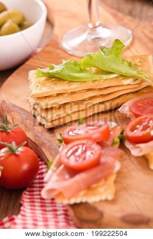 Crackers with ham and avocado on wooden table.