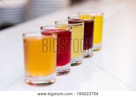 Multicolored alcoholic drinks stand on a white bar counter