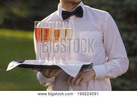 Waiter serving champagne on a tray outdoors