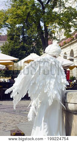 Lvov, Ukraine - 06.08.2016: Girl in form of an angel in city. White live angel statue