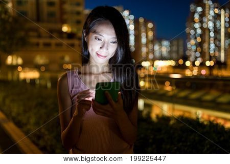Woman sending sms on cellphone in the evening