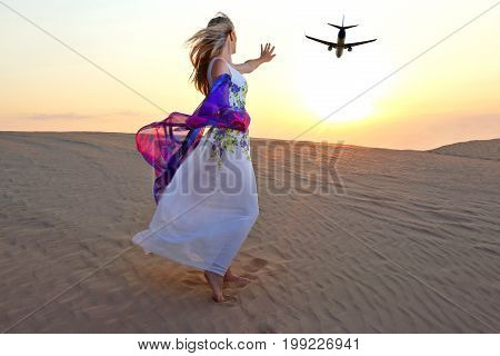 girl with raised hand sees a flying airplane in the desert in the sun