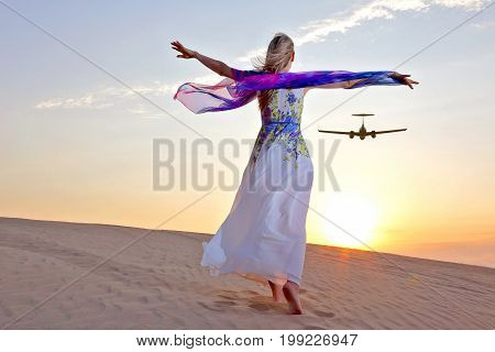 girl with raised arms accompanies flying plane in the desert in the sun