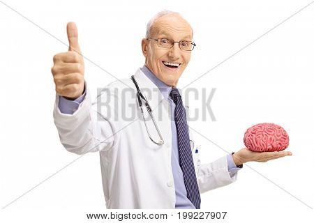 Elderly doctor holding a brain model and making a thumb up gesture isolated on white background