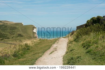 White chalk cliffs at Beachy Head near Eastbourne East Sussex England. With unrecognizable people in distance.