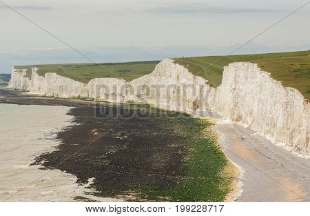 White chalk cliffs and shingle beach at Birling Gap near to Beachy Head at Eastbourne East Sussex England. Seven Sisters cliffs and Seaford Head in distance.
