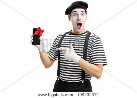 Mime artist showing a phone wrapped with red ribbon as a present and pointing isolated on white background