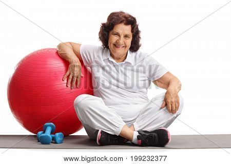 Elderly woman with a pilates ball and dumbbells sitting on an exercise mat isolated on white background