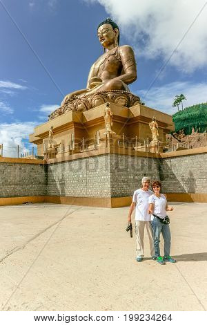 Couple smiling near giant Buddha Dordenma statue with the blue sky and clouds background Thimphu Bhutan South Asia