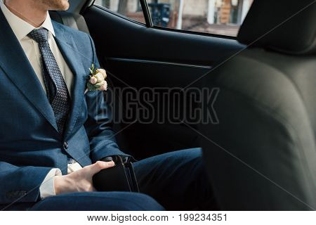 Groom in blue suit with boutonniere sitting on backseat inside the car at wedding day