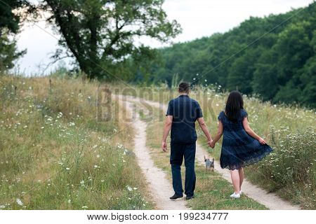 Couple In Love Holding Hands And Walking On Footpath With Yorkshire Terrier Dog Outdoors Near The Fo