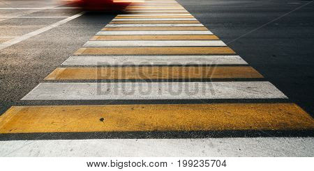 Yellow and white lines on the asphalt road pedestrian crossing. The concept of road safety.