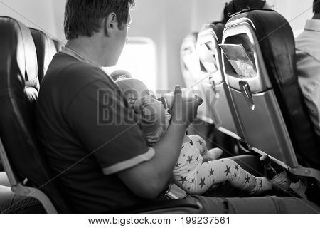 Father holding his baby daughter during flight on airplane going on vacations. Baby girl drinking formula milk from bottle. Air travel with baby, child and family concept.