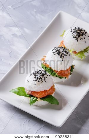 Mini rice sushi burgers with smoked salmon, green salad and sauces, black sesame served on white square plate over gray concrete background. Modern healthy food