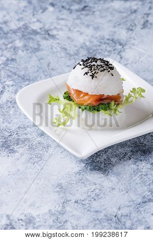 Mini rice sushi burger with smoked salmon, green salad and sauces, black sesame served on white square plate over gray concrete background. Modern healthy food
