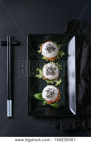 Mini rice sushi burgers with smoked salmon, green salad and sauces, black sesame served on black square plate with chopsticks and textile napkin over black background. Modern healthy food. Top view