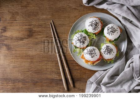 Mini rice sushi burgers with smoked salmon, green salad and sauces, black sesame served on gray plate with wooden chopsticks and textile over wood background. Modern healthy food. Top view with space
