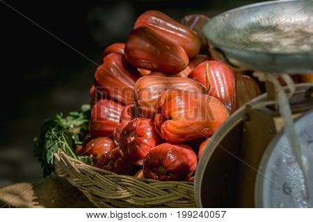 red rose apple is placed on a yellow rattan basket in the market.