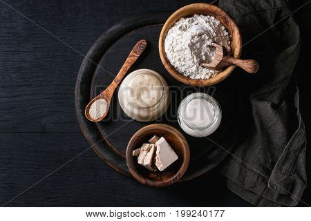 Rye and wheat sourdough in glass jars, fresh and instant yeast, olive wood bowl of flour for baking homemade bread. With spoon, serving board, textile over black burned wooden background. Top view