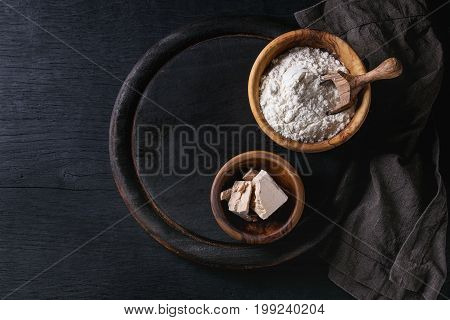 Fresh organic broken yeast cube, olive wood bowl of flour for baking homemade bread. With scoop, serving board, textile over black burned wooden background. Top view with copy space