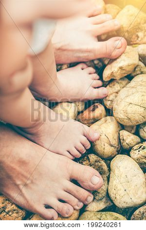 Child's foot learns to walk on pebbles with father together. Healthy family spending time outdoor on summer day with sunlight. Concept of first steps and development learning in young children.