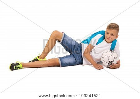 A teen male laying with a soccer ball isolated on a white background. A schoolboy relaxing and having fun with a ball. A blond kid in light casual clothes with a blue backpack. School club membership.