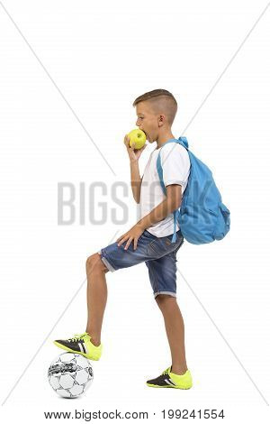 A student boy eating a fresh fruit isolated on a white background. A schoolboy with a green apple and a soccer ball. A pupil in light summer clothes with a backpack. Getting ready for school concept.