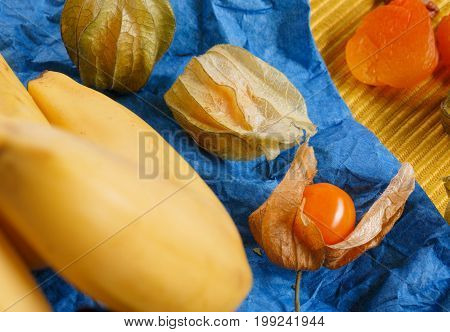Closeup of vivid orange dried apricots, unpeeled sappy juicy physalis, bright yellow bananas on a dark blue napkin on a colorful background. Sweets, fruits concept.