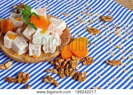 Close-up of turkish delight, lokum or rahat lokum, bright dried apricots on a wooden plate, leaves of mint, walnuts, crumbs of walnuts on the table on a striped background.