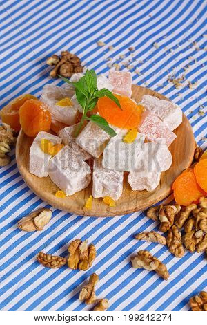 Close-up of turkish delight or rahat lokum, dried apricots with green leaves of mint, walnuts and crumbs of walnuts on a wooden plate on a striped background.