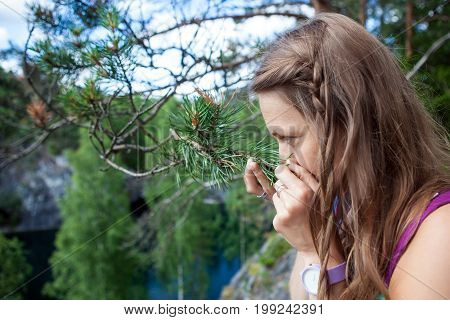 blonde girl enjoying the smell of pine needles in the forest