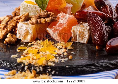 Sweets concept. Copy space. A plate with lokum, rahat lokum or turkish delight, brown date fruits, walnuts and mint on a striped tablecloth and on a dark plate, close-up.