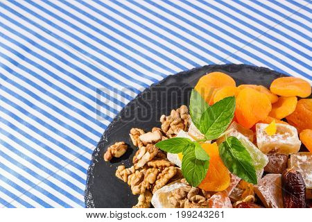 Closeup of dry apricots, turkish delight, lokum or rahat lokum, sweet date fruits, walnuts, bright aromatic leaves of mint on a striped background, top view. Sweets concept. poster