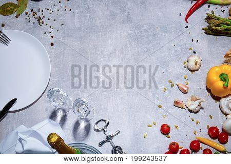 Bright yellow bell pepper, tomatoes, garlic and chili pepper on a gray stone background. A view from above on a beautiful composition. A plate with a cutlery next to different bright raw vegetables.