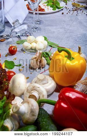 A close-up picture of yellow and red bell peppers, mushrooms, garlic, tomatoes, potatoes, cucumber, and salad leaves. Still life. Fresh ingredients for healthy dinner dishes. Food and cooking concept.