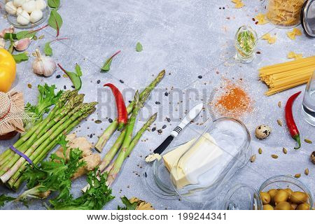 A beautiful composition of various healthy ingredients on a gray table background. Greens, asparagus, hot chili pepper, spices and a butter knife with a butter in a glass box. Raw pasta. Food concept.