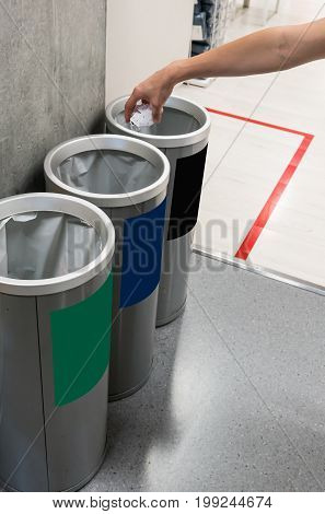 Woman hand putting used paper in recycled bin. Different color trash cans in row for waste management. Perspective disposal view for saving environmental concept.