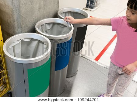 Asian little girl putting used paper in recycled bin. Different color trash cans in row for waste management. Perspective disposal view for saving environmental concept.