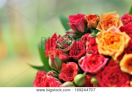 Closeup of wedding rings with pink flowers