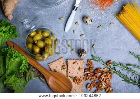Different foods on a gray background. Nutritious walnuts, raw pasta, pickled fruits, fresh salad, green rosemary, quail, ginger, eggs. A wooden spoon and bread slices. Traditional pasta preparation.