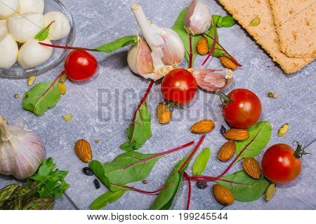 A close-up picture of fresh salad ingredients on a gray stone background. Red cherry tomatoes, green salad leaves, almond nuts, bread slices, garlic and peeled potato. Healthy salads full of vitamins.