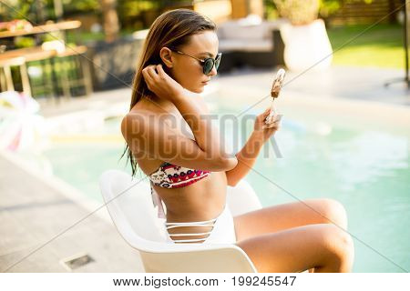 Pretty Young Woman With Ice Cream On The Poolside