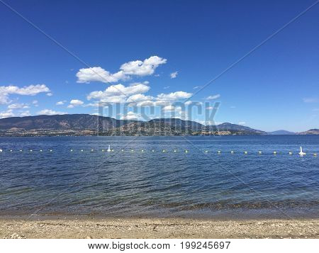 Scenic summer lake and mountains landscape view with sandy beach. Cloud reflections on water and rock in water on shoreline.