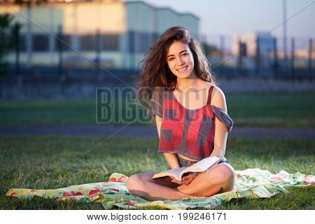 Young Woman student Enjoying a Book Reading Outdoors