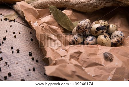 A pile of beautiful quail eggs on a crumpled paper on a wooden table background. Nutritious uncooked quail eggs. Protein ingredients for rustic homemade dishes. Boiled eggs with black pepper.