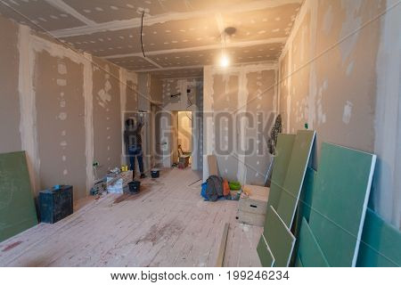 Worker prepares walls for remodeling it by drywall (plasteboard gypsum) and interior of apartment with materials during on the renovation and construction.