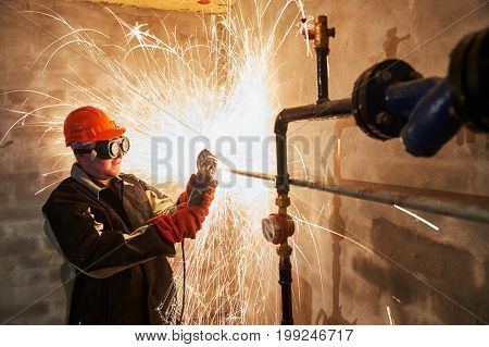 worker cutting pipe with sparks by grinder flame torch cutter