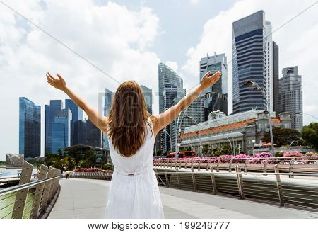Young Woman With Raised Arms On Skyscrapers Background